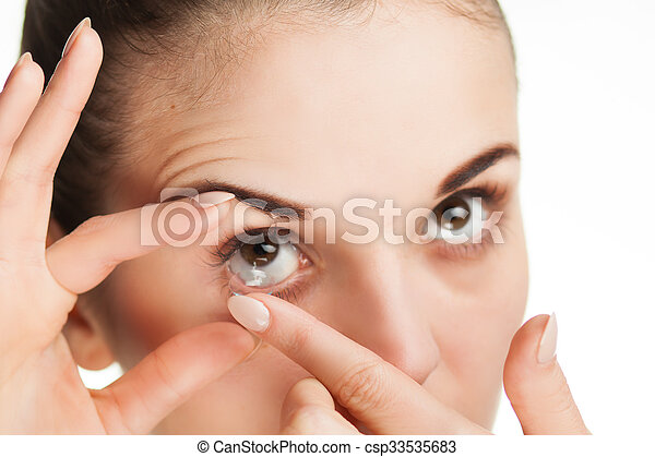 Woman putting contact lens in her eye - csp33535683