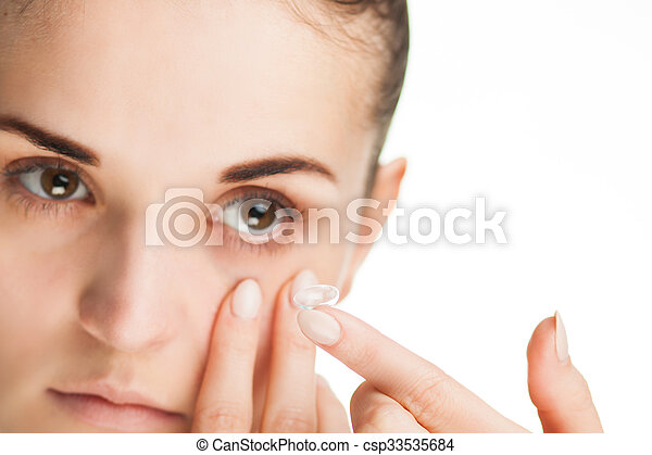 Woman putting contact lens in her eye - csp33535684