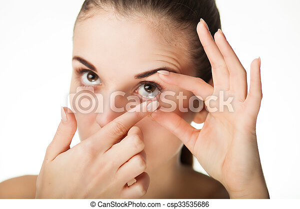 Woman putting contact lens in her eye - csp33535686