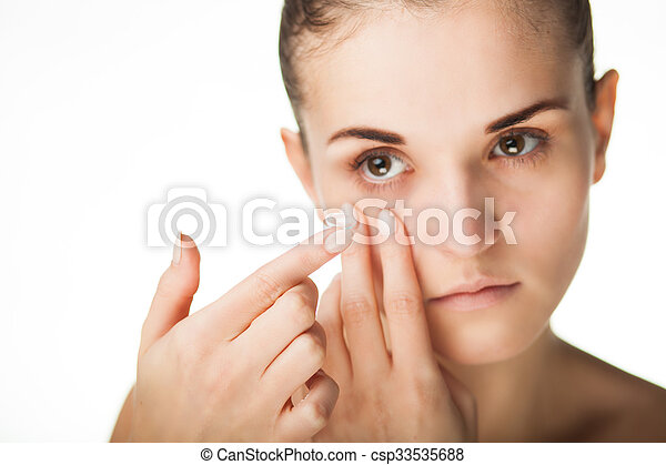 Woman putting contact lens in her eye - csp33535688
