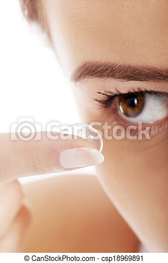 Woman putting contact lens in her eye - csp18969891