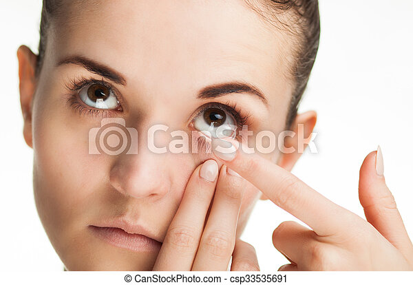 Woman putting contact lens in her eye - csp33535691
