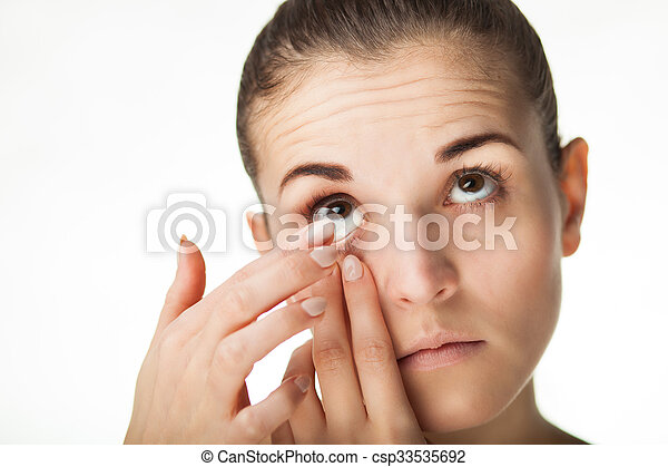 Woman putting contact lens in her eye - csp33535692