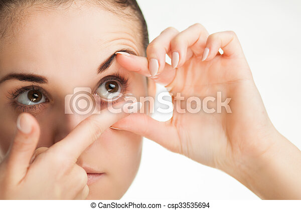 Woman putting contact lens in her eye - csp33535694