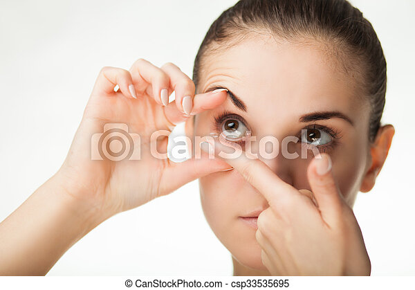 Woman putting contact lens in her eye - csp33535695