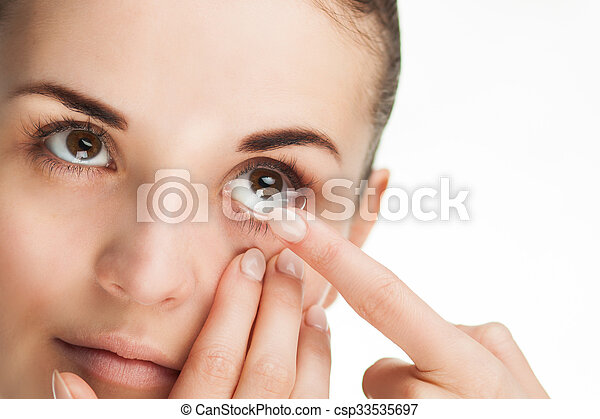 Woman putting contact lens in her eye - csp33535697