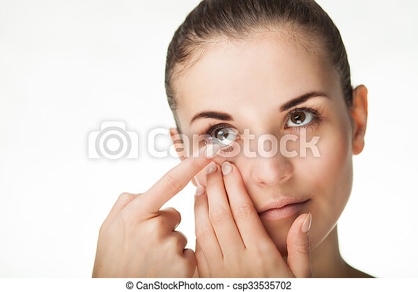 Woman putting contact lens in her eye - csp33535702