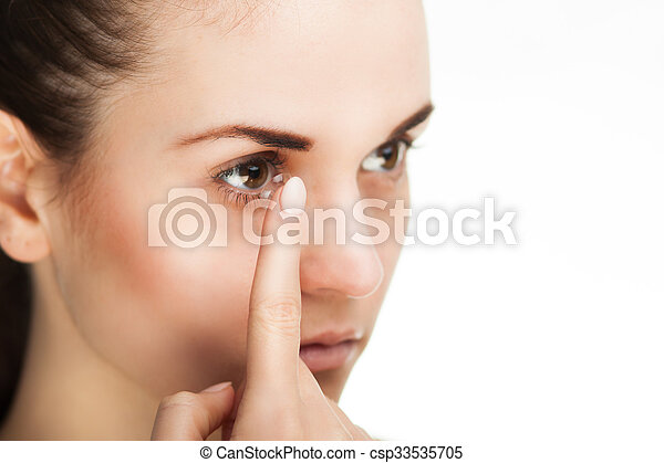 Woman putting contact lens in her eye - csp33535705