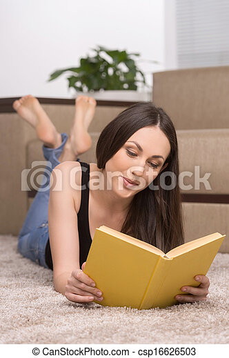 Woman reading a book. Beautiful young woman lying on the floor at home and reading book - csp16626503