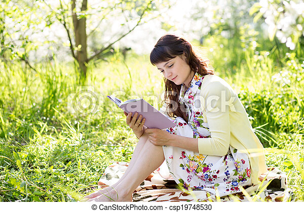 woman reading a book sitting on grass - csp19748530