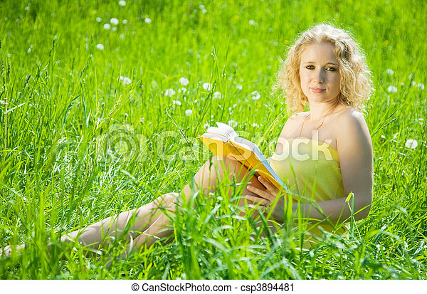 woman reading book in grass - csp3894481
