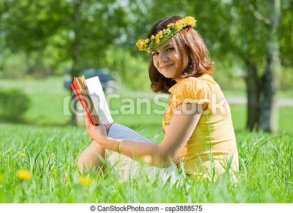 woman reading book in grass - csp3888575