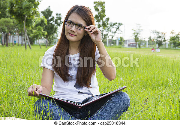 Woman reading  on the grass - csp25018344