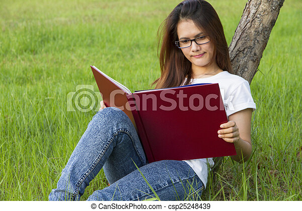 Woman reading  on the grass - csp25248439