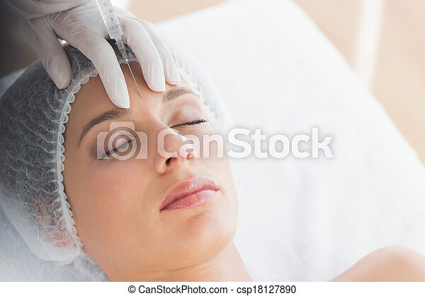 Woman recieving botox injection in forehead - csp18127890