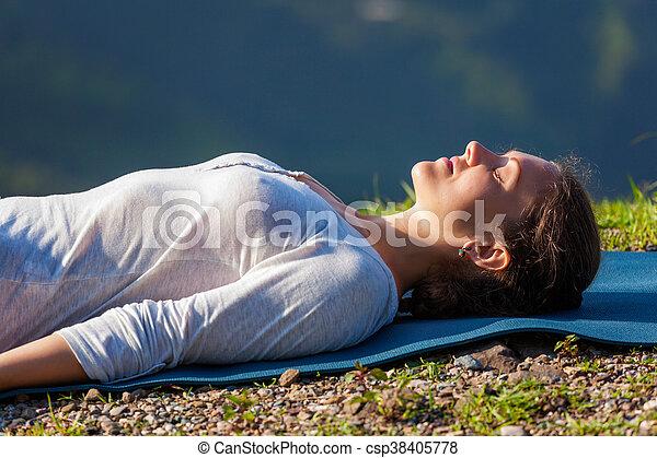 woman relaxes in yoga asana savasana outdoors woman