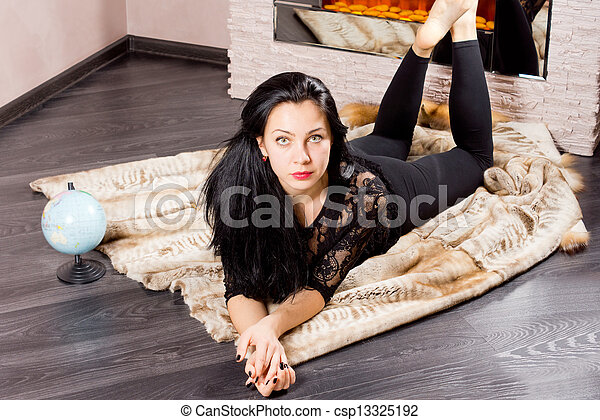 Woman relaxing in front of a winter fire - csp13325192