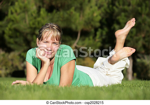 Woman relaxing on a lawn with a nice defocused background - csp2028215