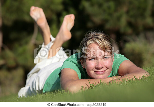 Woman relaxing on a lawn with a nice defocused background - csp2028219