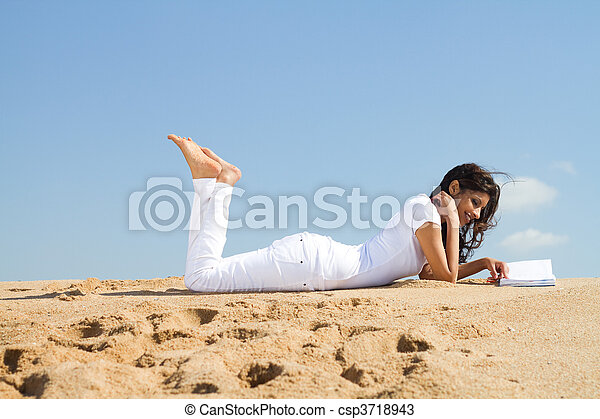 woman relaxing on beach with book - csp3718943
