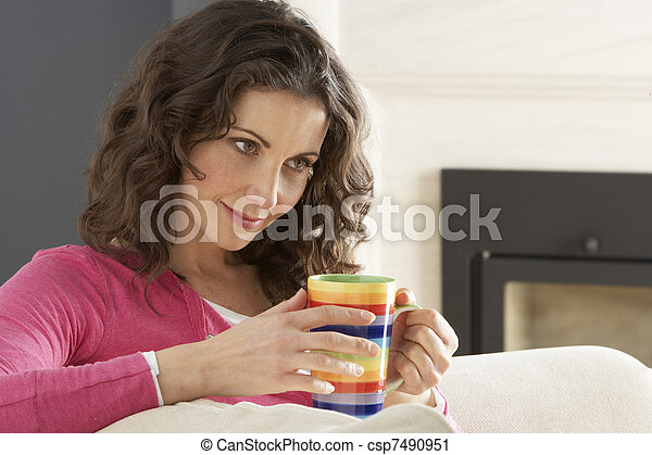 Woman Relaxing On Sofa At Home Drinking Cup Of Coffee - csp7490951