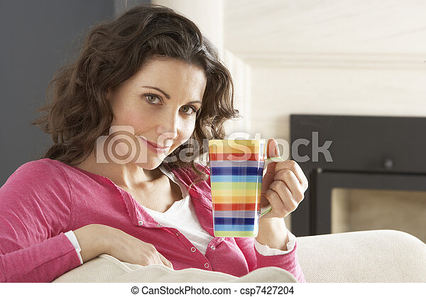 Woman Relaxing On Sofa At Home Drinking Cup Of Coffee - csp7427204