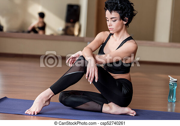 young attractive woman relaxing on yoga mat after workout