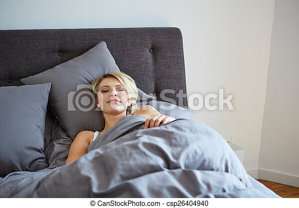 woman resting in bed with hands beside her head - csp26404940