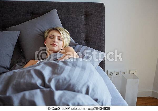 woman resting in bed with hands beside her head - csp26404939