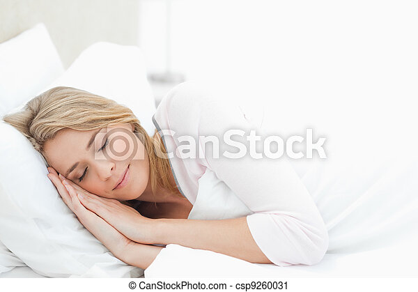 Woman resting in bed, with hands by her head - csp9260031