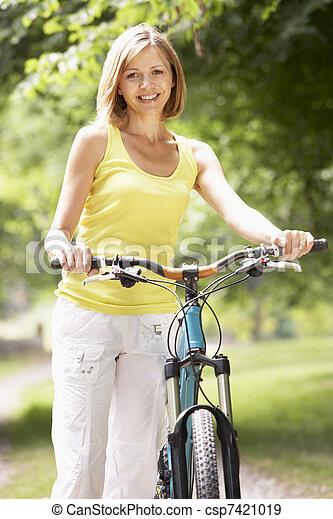 Woman riding bike in countryside - csp7421019