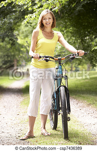 Woman riding bike in countryside - csp7436389