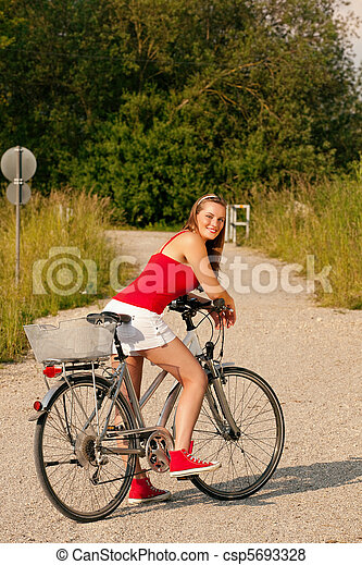 Woman riding her bicycle in summer - csp5693328