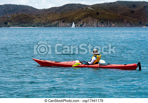 woman rows a sea kayak in the bay of island new zealand very