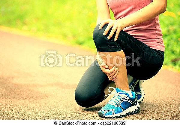 woman runner hold her injured knee - csp22106539
