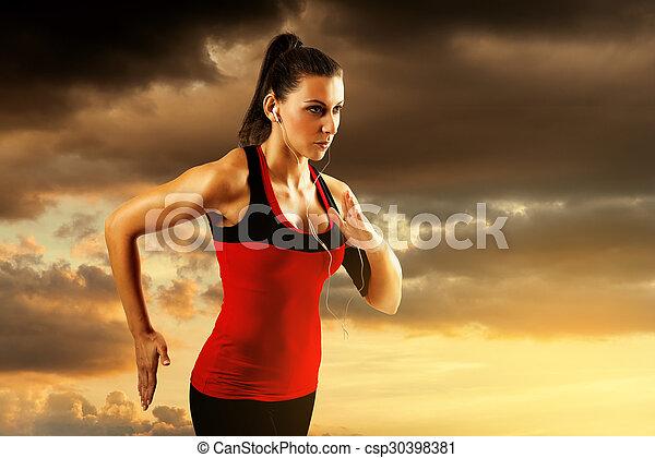 Woman running at sunset. - csp30398381