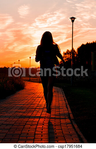 Woman running in the city on sunset time - csp17951684