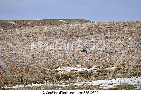 Woman running in the field - csp66542509
