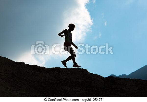 Woman runs downhill on mountain trail - csp36125477