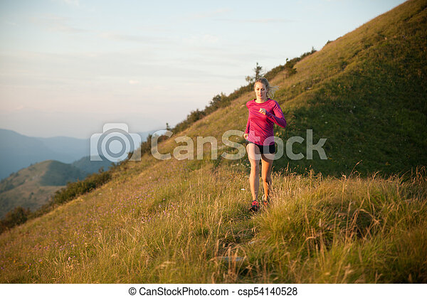 Woman runs on a top of the mountains with mountain range in background - csp54140528