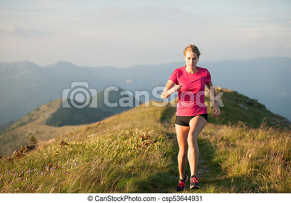 Woman runs on a top of the mountains with mountain range in background - csp53644931