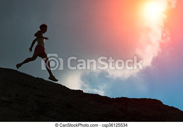 Woman runs on the ridge with colorful sun - csp36125534