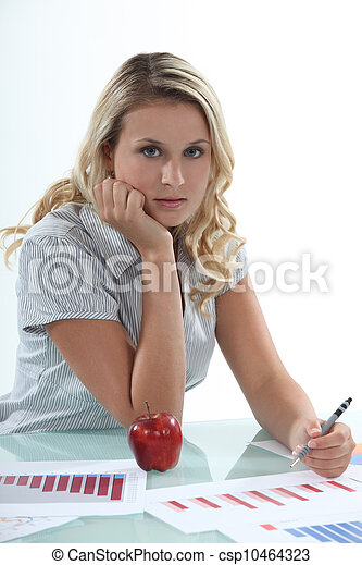 Woman sat at desk working on graphs - csp10464323