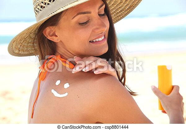 Woman sat on the beach applying sun cream - csp8801444