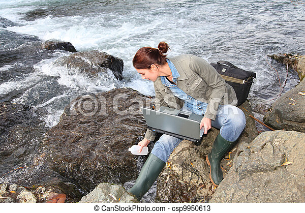 Woman scientist testing quality of water in river - csp9950613