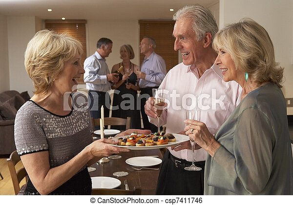 Woman Serving Hors D'oeuvres To Her Guests At A Dinner Party - csp7411746