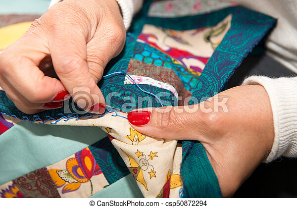 woman sewing for finish a quilt. - csp50872294