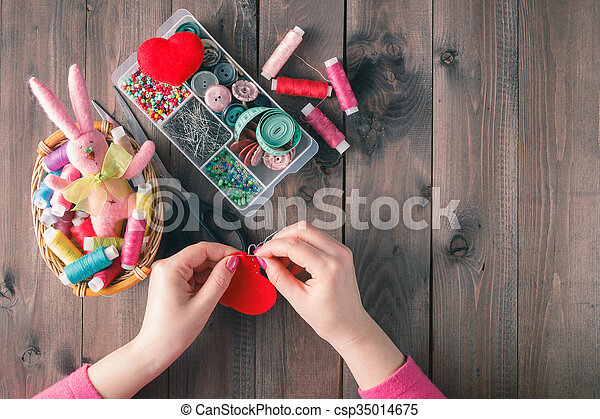 Woman sews red heart shaped toy by needle - csp35014675