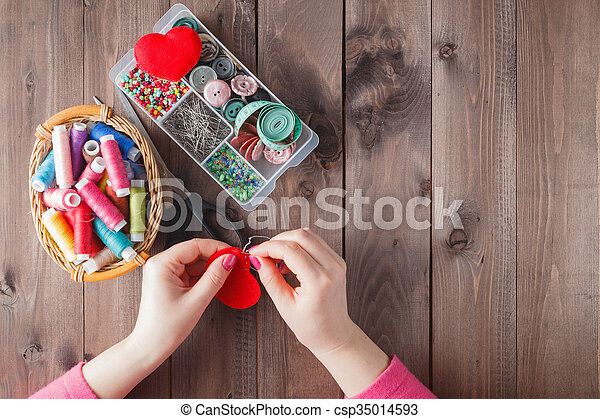 Woman sews red heart shaped toy by needle - csp35014593