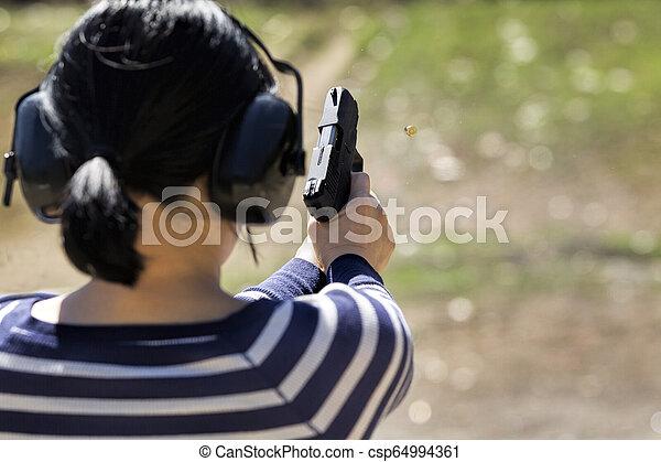 Woman shoots pistol at range. - csp64994361